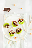 Kiwi lollipops with melted chocolate and chopped hazelnuts