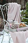 Tablett mit Windlicht, Gebäck und Tassen auf Stuhl mit Decke
