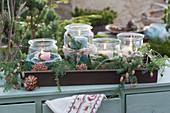 Einmachgläser mit Kerzen und Zweigen als Adventskranz
