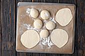 Pitabrot selbermachen: Teiglinge und ausgerollte Fladen auf Ofenblech