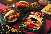 Appetizing burgers with tomatoes and crispy chicken on dark plates in gastrobar