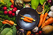 Two fresh farm carrots in vintage bowl and assorted organic vegetables on rustic black concrete background