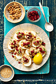 Curry-colored eggs filled with lentils, nuts and pomegranate seeds