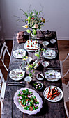 A table laid for Easter with a spring salad, roasted carrots, and carrot cake