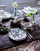 Gedeckter Ostertisch mit Frühlingsblumen und Eiern