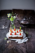 Carrot cake with a cream cheese topping, spring flowers and a teapot