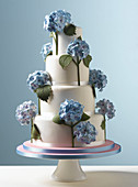 Easter Celebrations, tiered white wedding cake with blue hydrangea flowers with a pale blue background