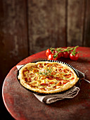Tomato quiche with puff pastry on a round red metal table