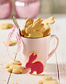 Rabbit shaped biscuits in a coffee cup on a white wooden table