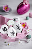 Easter eggs decorated with monochrome stickers in pink egg box