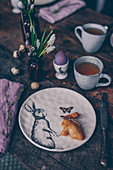 A table laid for an Easter breakfast with tea and an Easter bunny bun
