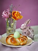 A coloured Easter egg in a bread wreath nest on an Easter table
