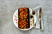 A small chocolate cake with colourful chocolate pearls