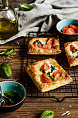 Puff pastries topped with mozzarella, cherry tomatoes and basil oil