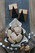 Gluten-free shortbread biscuits with hazelnuts in a Christmas tree bowl with Christmas garlands and decorations