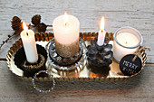 Four burning candles with Christmas decorations on a tray