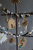 Christmas-tree decorations on stylised tree handmade from twigs