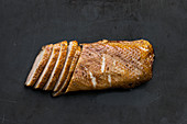 Smoked duck breast fillet on an industrial black background