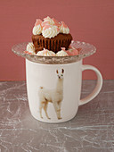 A quark cupcake on top of a llama coffee cup