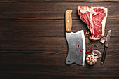 A raw T-bone steak with spices, a knife and a cleaver on a wooden surface