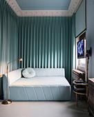 Hellblaues quadratisches Bettsofa in Zimmerecke mit Vorhängen, Flatscreen und Rollo