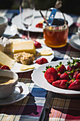 A table outside laid with coffee, strawberries, a cheese platter and jam