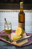 A bottle of elderflower syrup behind a sliced lemon on a wooden surface
