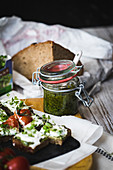 Pesto in a flip-top jar with a slice of bread topped with cream cheese and cress