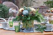 Weihnachtsstrauß in goldener Vase als Tischdekoration