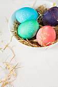 Coloured Easter eggs in a bowl of straw