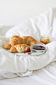 Breakfast in bed with croissants and jam