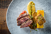 Smoked saddle of lamb with oriental ratatouille curry soubise