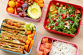 Creative layout with healthy lunch dishes variety in bento boxes on wooden table