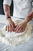 Pizza dough being kneaded