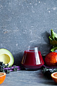 A glass of beet juice surrounded by fruits and vegetables