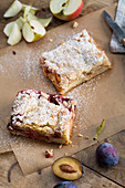 A slice of apple tray bake cake and a slice of damson tray bake cake