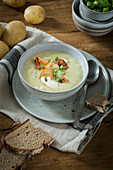 Potato soup with spring onions and fried bacon