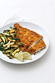 Breaded plaice fillet with fried zucchini and lemon