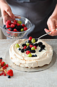Berries being added to pavlova