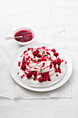 Quick Pavlova with whipped cream, raspberry coulis and pomegranate seeds