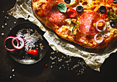A pizza topped with salami, olives, peperoni and onions (close-up)