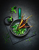 Mange tout with colourful carrots in a pan