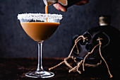 An Easter cocktail with eggnog, rum, espresso, with coconut flakes on the rim of the glass