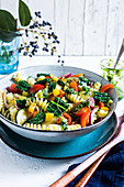 A bowl with pasta salad with kale, cherry tomatoes, roasted peppers, roasted zucchini and pickled red onions. Drizzled with kale pesto.