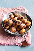 Bignole al cioccolato (fried puff pastry balls with chocolate cream, Italy)