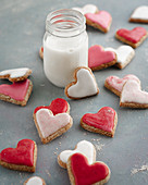 Pink, red and white heart-shaped biscuits with a glass of milk