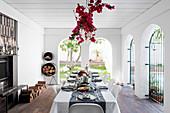 Festlich gedecker Tisch, darüber Bougainvillea-Dekoration