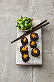 Pumpkin sushi with black rice served with edamame