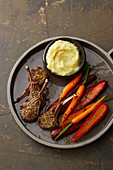 Lamb chops with a herb crust, mashed potatoes and carrots