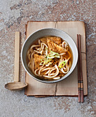 Japanese dashi broth with udon noodles and fried tofu